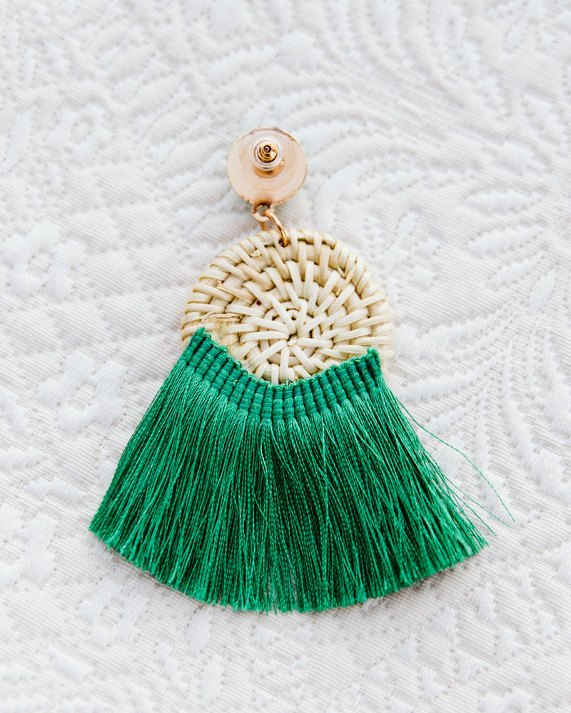 back of statement earrings with woven straw disc and green tassels