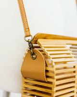 detail of wooden rectangular bamboo purse with crossbody strap