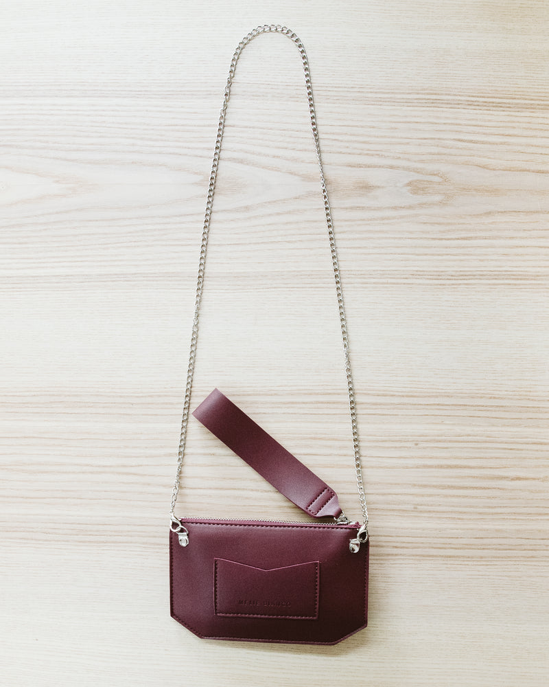 model holding burgundy wine red wristlet wallet purs