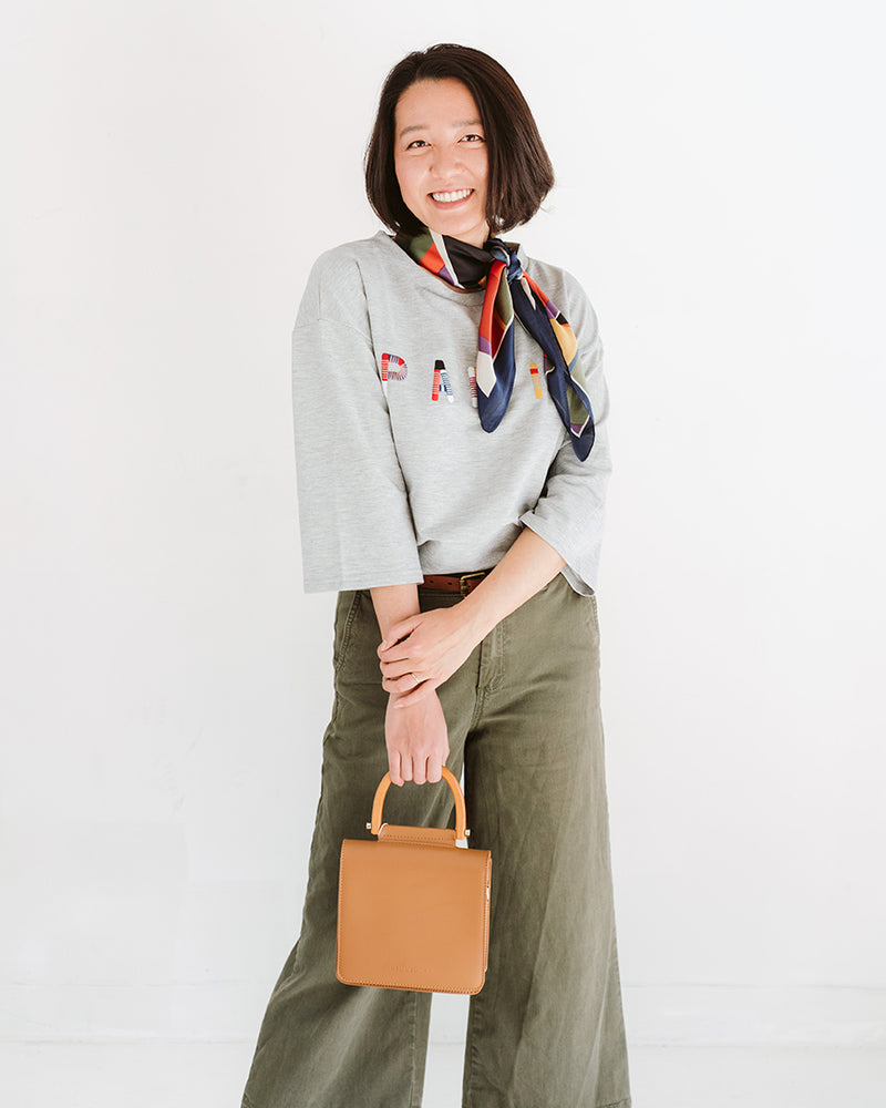 model wearing camel tan rectangle vegan leather purse with wood handle