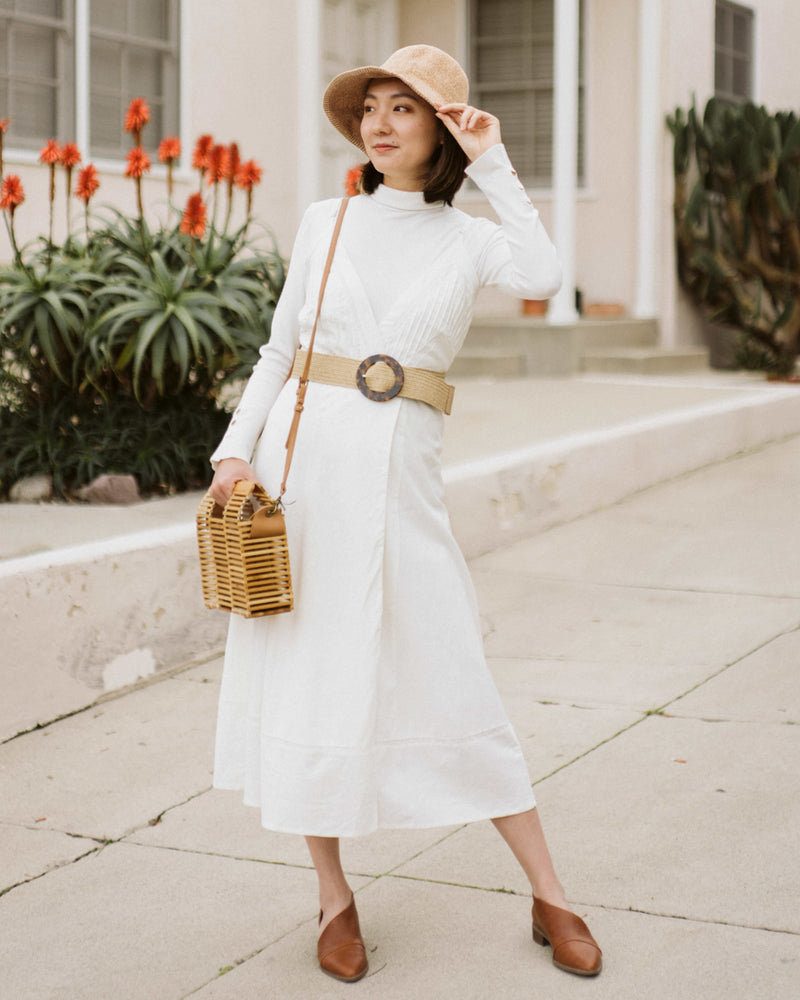 model wearing white wrap spaghetti strap dress with lace