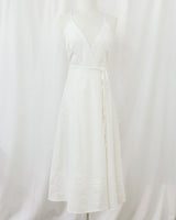 mannequin wearing white wrap spaghetti strap dress with lace