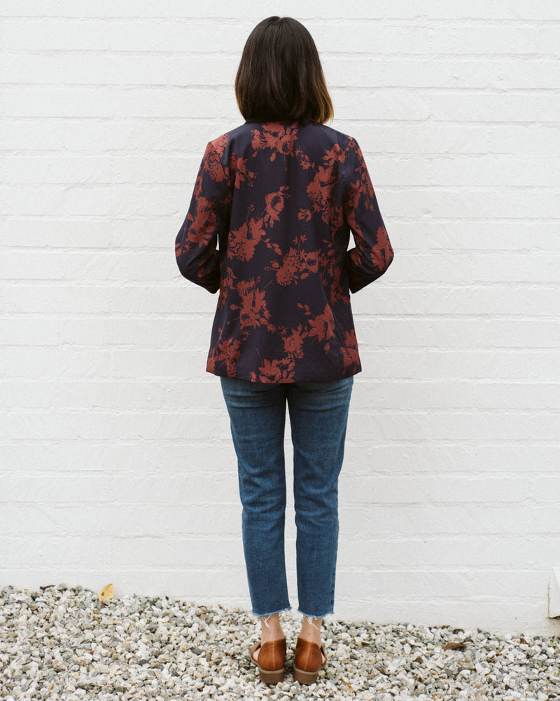 back detail of navy blue and rust red floral print blazer