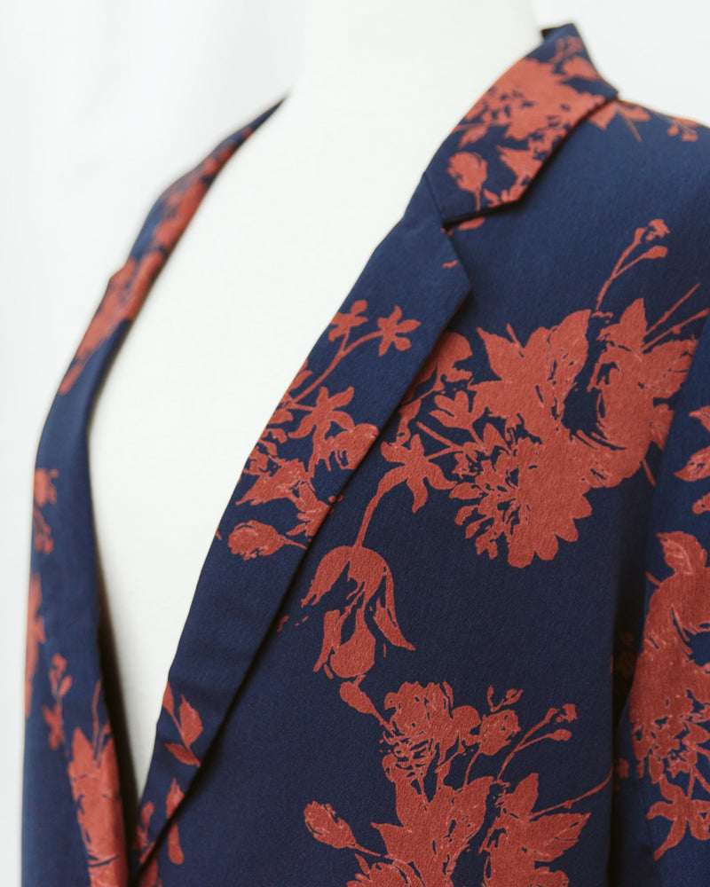 collar detail of navy blue and rust red floral print blazer