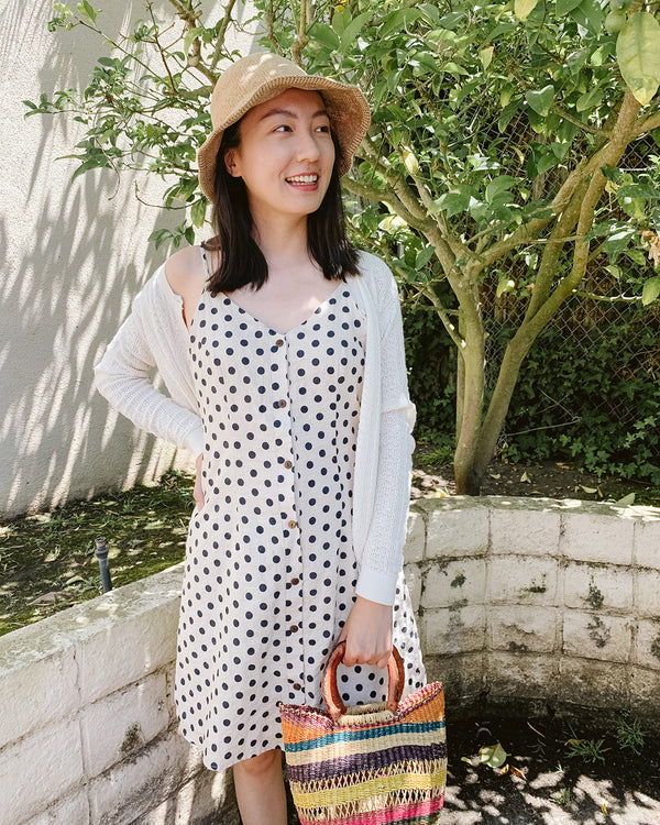polka dot cream and navy dress and woven bucket hat