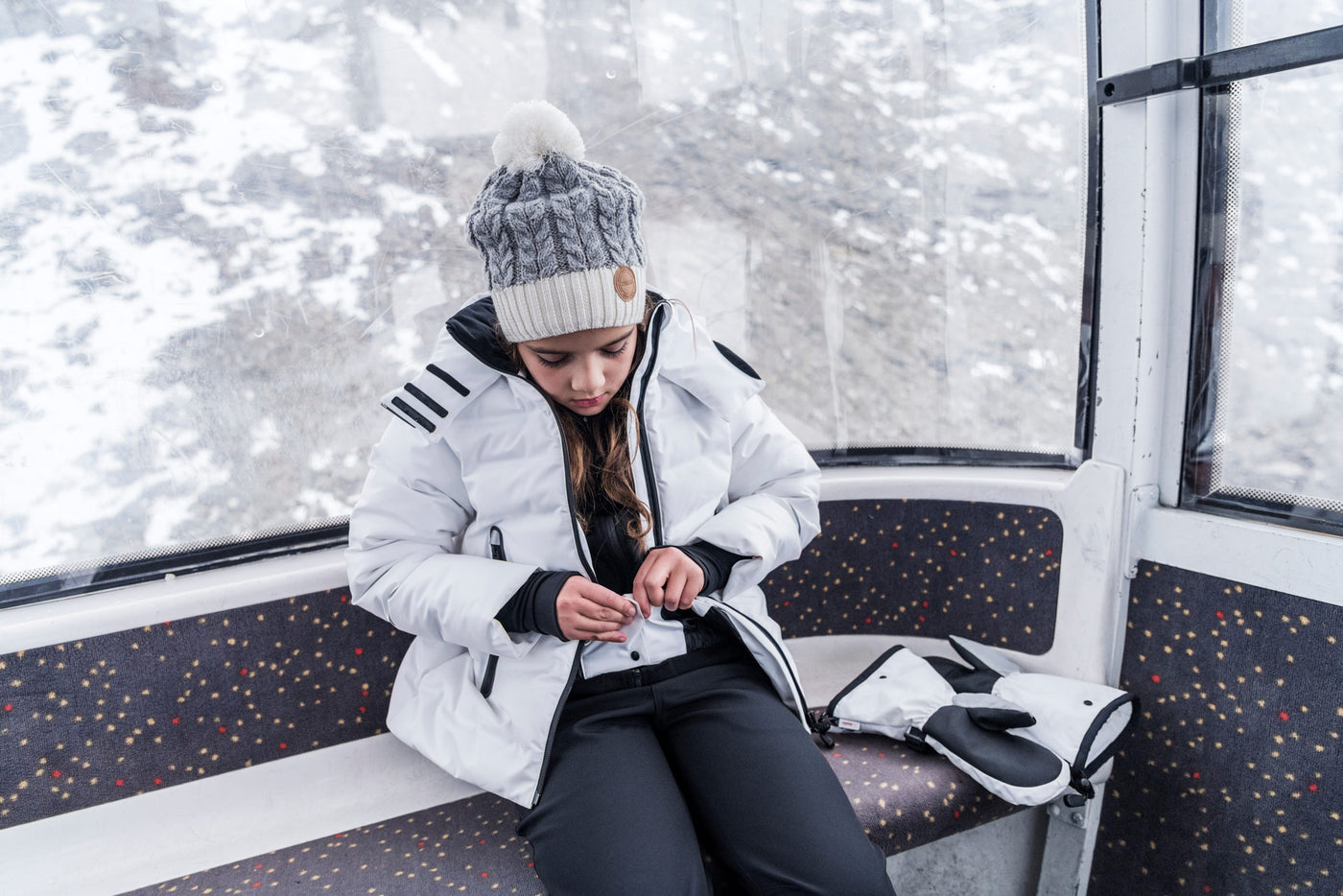 Girl in ski jacket zipping up her midlayer jacket in a ski enclosed gondola with gloves alongside