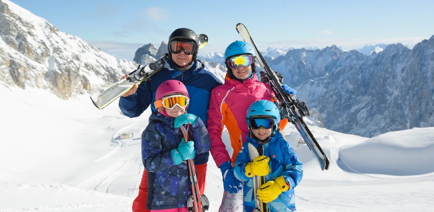 image of family of four with skis at the snow resort