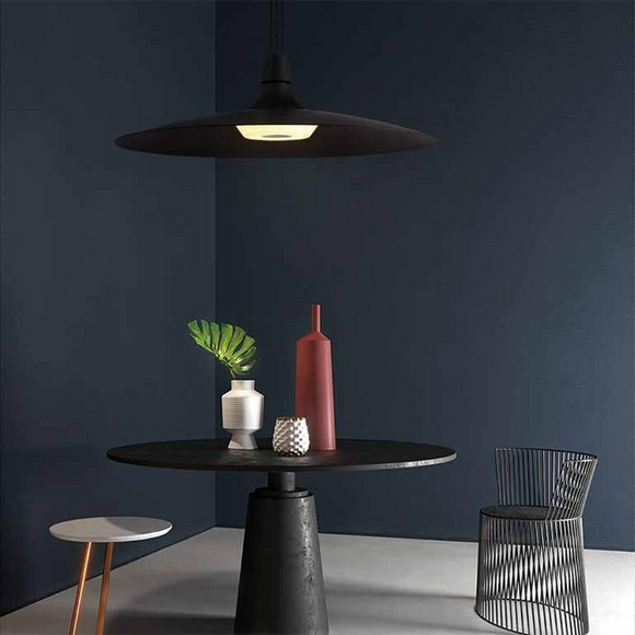 modern black and copper wide shade pendant mounted over a sleek circular dining table