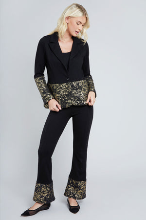 Black bell bottom pant with gold foil trim on the bottom of each leg