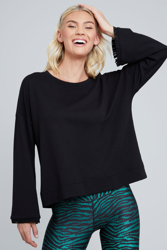 Loose fitting, black, long bell sleeve shirt with fringe at the ends of the sleeve