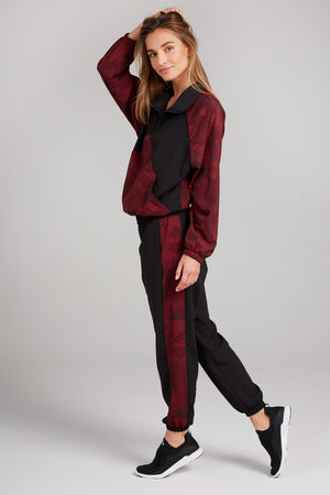 Black track pants, with deep red striped camo panels on the side of each leg