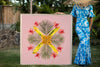 Woman in a hawaiian mumu holding a large 4ftx4ft of the Pink Palace photographic art inspired by the hawaiian quilt