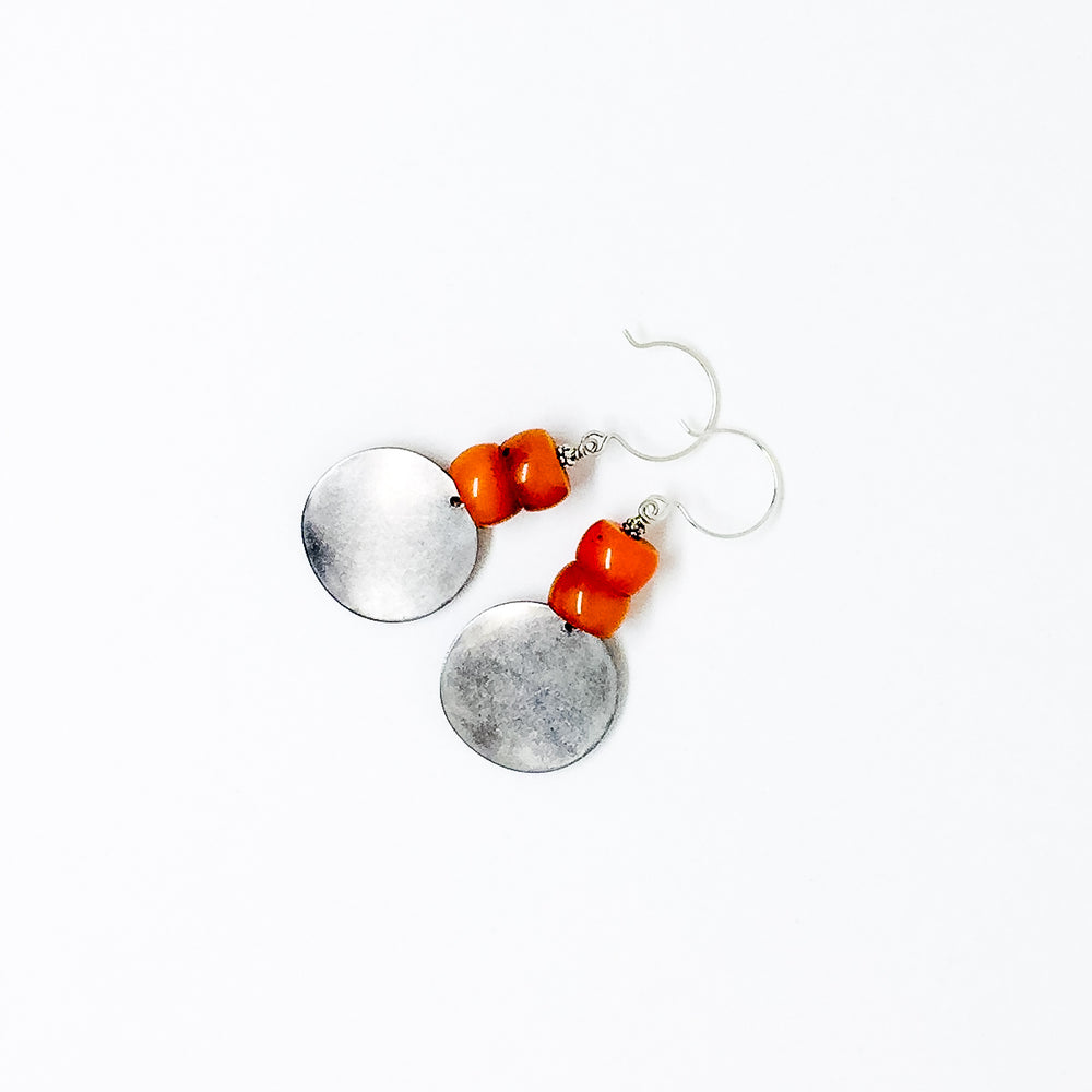 Matte silver-tone discs and deep orange resin bead earrings flat lay