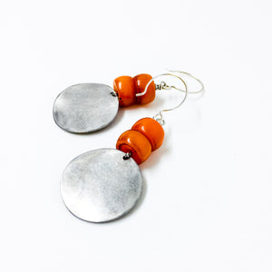 Matte silver-tone discs and deep orange resin bead earrings