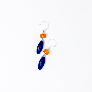 Contrasting orange resin and cobalt Czech glass drop earrings flat lay