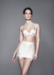 The cream elastic waspie is a signature Bordelle piece made from panels of wide lustrous elastic and fastened with an open end 24k gold plated zip on the centre back. Wear in the boudoir with sheer stockings or as a micro mini over opaque tights for a daring party outfit.