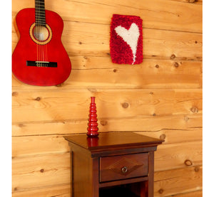 "Handwoven wall hanging rug on log wall, white heart figure on red background,  20 x 30 cm, 7,87 x 11,8""."