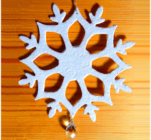 White flax felt decoration snowflake, with crystal stone, on log wall.