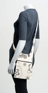 asymmetric shoulder bag, 100 % cotton, off white with gray flowers, long strap, on a manikin, sits wonderfully on the hips, back.