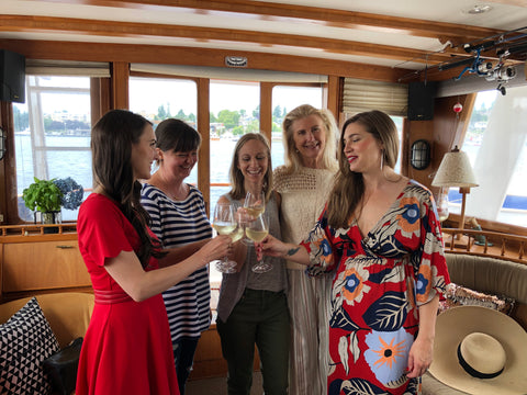 women clinking glasses of champagne on a vintage yacht