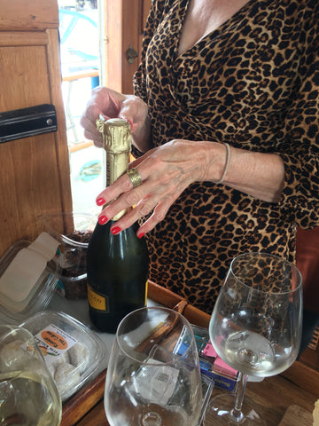 woman popping open champagne with red manicure and leopard dress