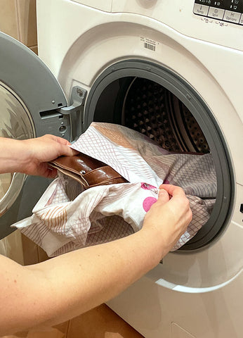Enclose your bag inside an old pillowcase and put your bag in the washing machine
