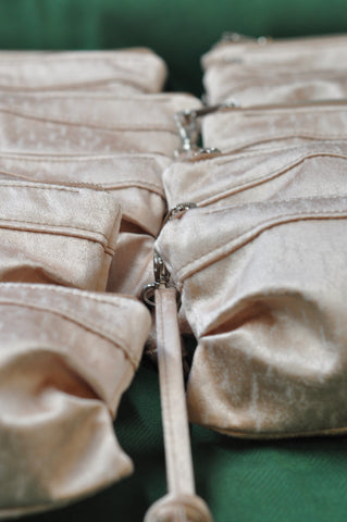 a row of ivory silk clutches for a wedding party bridesmaid gift