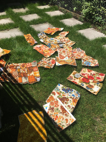 vintage fabric swatches laying in a grassy yard