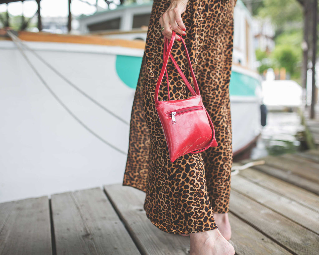 woman in leopard print dress holding a strap of Cha Cha Small Crossbody Bag - Cherry Red Vegan Leather