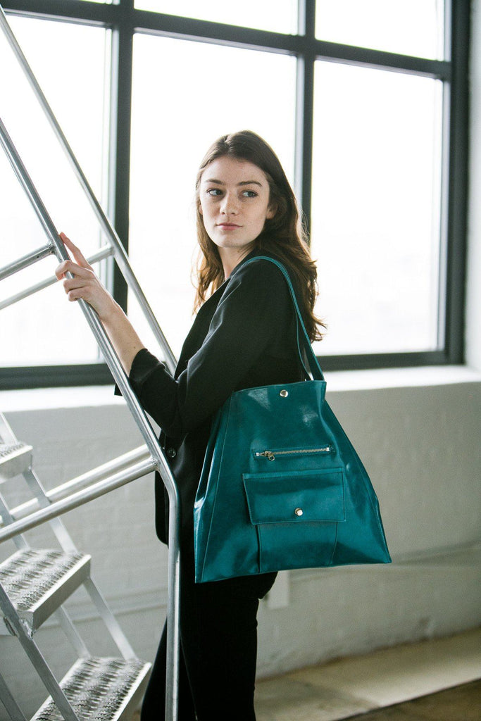 woman climbing corporate ladder wearing Womens Tote Bag - Metier Tote - Teal Vegan Leather