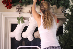 Girl putting up pet stockings on a mantle
