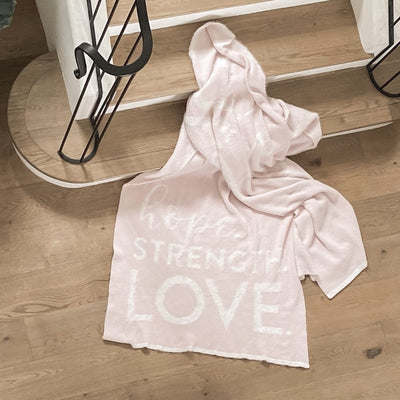 Hope Strength Blanket from the Dream Collection laying on wooden stair case, micro-chenille and feather yarn, light pink blanket BIG LOViE