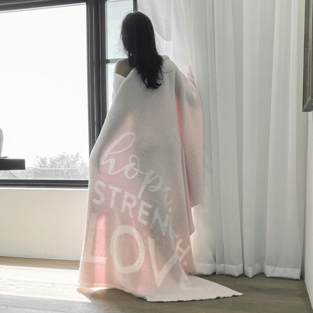 Woman standing by window, draped in Hope Strength Blanket from Dream Collection, micro-chenille and feather yarn, light pink blanket BIG LOViE