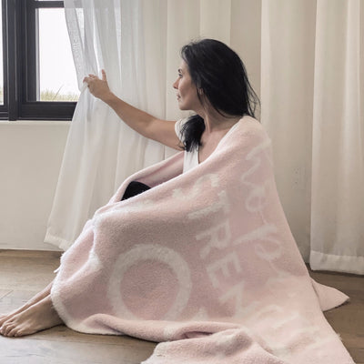 A woman wrapped in the Hope Strength Blanket gazing out window, light pink blanket, micro-chenille and feather yarn