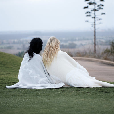 Two woman sitting together on grass, wrapped in Love and Wings Blanket from the Dream Collection, micro-chenille and feather yarn