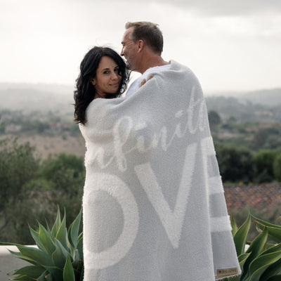 Couple standing on deck wrapped in Love Blanket from the Dream Collection, micro-chenille and feather yarn, light grey blanket