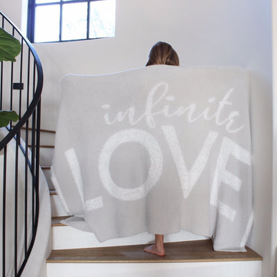 Young girl standing on stairs, arms spread out holding the Love Blanket from the Dream Collection, micro-chenille and feather yarn, light grey blanket