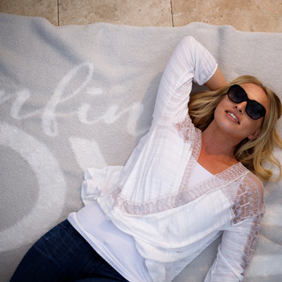 Woman lounging in sunglasses, laying on Love Blanket from Dream Collection, micro-chenille and feather yarn, light grey blanket