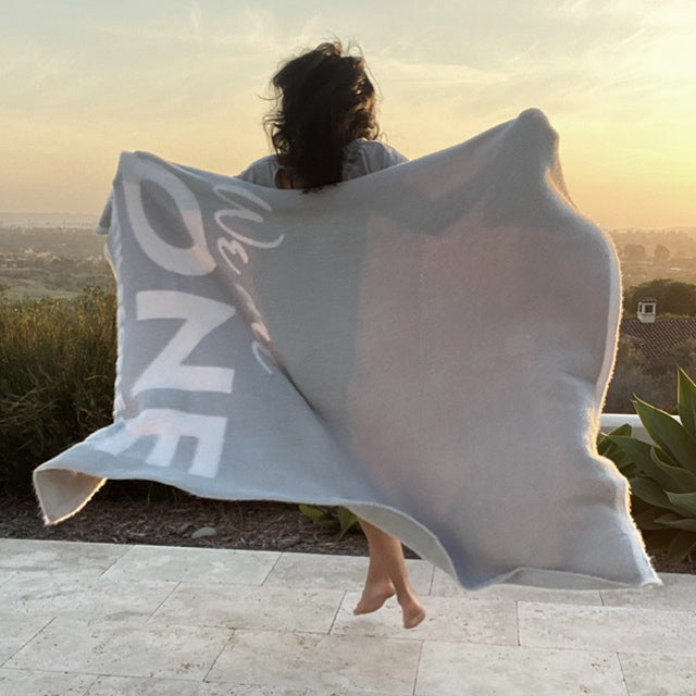 Woman jumping outside at sunset, wrapped in her One Blanket from the Dream Collection, micro-chenille and feather yarn