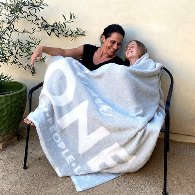 Mother and daughter sitting on chair together, smiling, in One Blanket from Dream Collection, micro-chenille and feather yarn