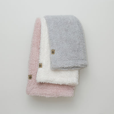 Stacked llama fabric blankets from the Guardian Angel Collection in: Silver Cloud, Whisper White, Dusty Pink