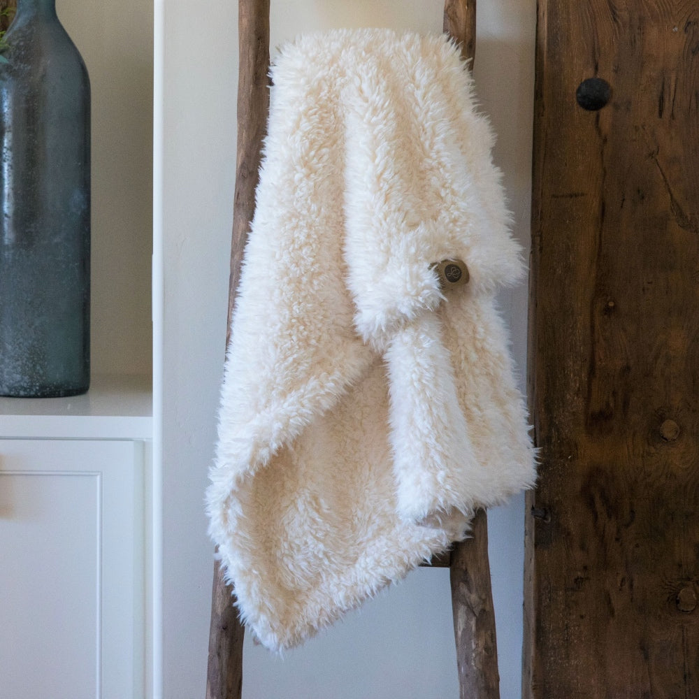 Little Guardian Angel blanket in Whisper White, llama fabric, on wooden ladder in front of white cabinets BIG LOViE