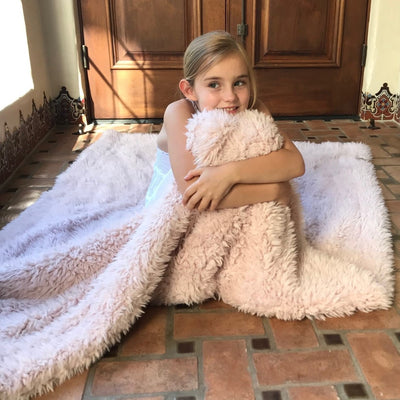A little girl sitting on the floor, cuddled in her big guardian angel blanket, dusty pink, llama fabric