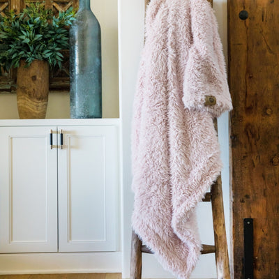Big Guardian Angel blanket in Dusty Pink, llama fabric, on a wooden ladder in front of white cabinets