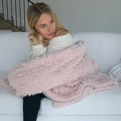 A woman sitting on a sofa wrapped in her big guardian angel blanket, dusty pink, llama fabric