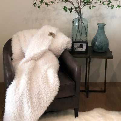 Whisper White Guardian Angel Blanket draped over leather chair