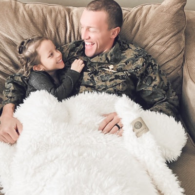 Military dad and daughter snuggled in their Big Guardian Angel Blanket in Whisper White, plush llama fabric