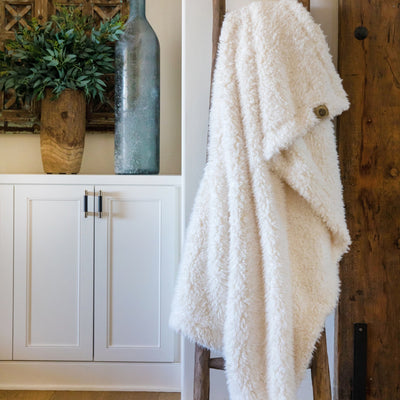 Big Guardian Angel blanket in Whisper White, llama fabric, on a wooden ladder in front of white cabinets