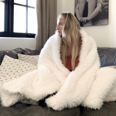 A woman on a couch snuggled in her Big Guardian Angel Blanket in Whisper White, plush llama fabric