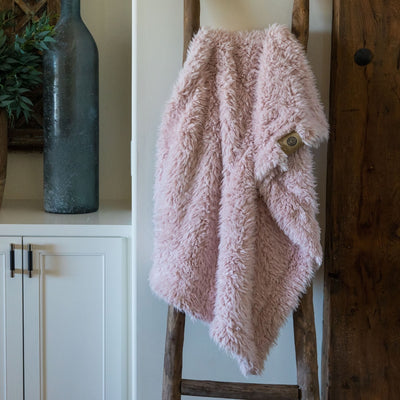 Little Guardian Angel blanket in Dusty Pink, llama fabric, on a wooden ladder in front of white cabinets
